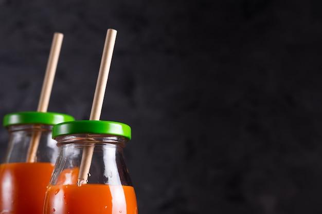 Морковный и апельсиновый сок в стеклянных бутылках с эко-соломкой в сдержанном ключе крупным планом