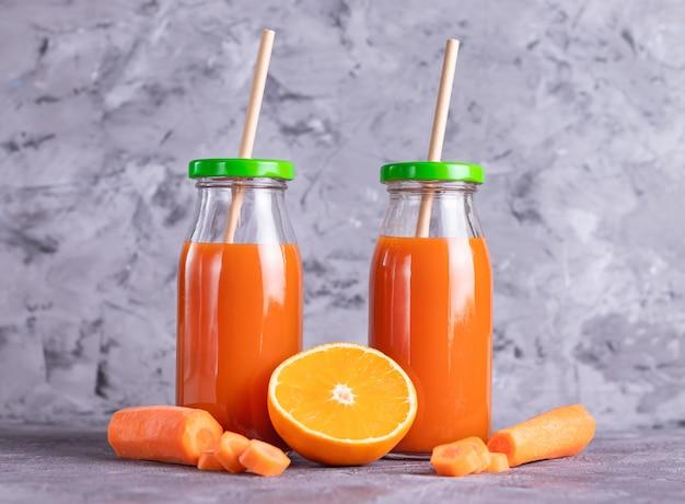 Морковный и апельсиновый сок в стеклянных бутылках с эко-соломкой на светлом фоне