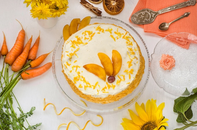 Carrot cake day. carrot cake on a white plate decorated with orange zest and peaches with yellow flowers and carrots. view from above. homemade cakes