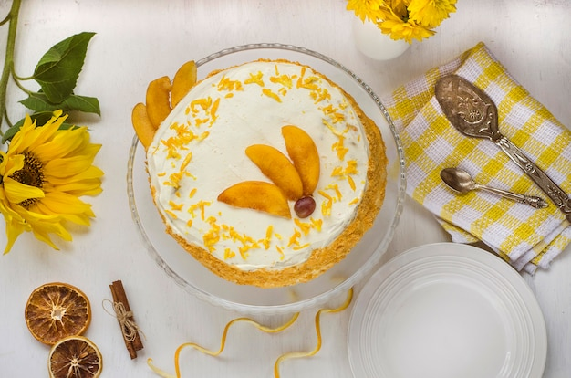 Carrot cake day. carrot cake on a white plate decorated with orange zest and peaches with yellow flowers. view from above. homemade cakes