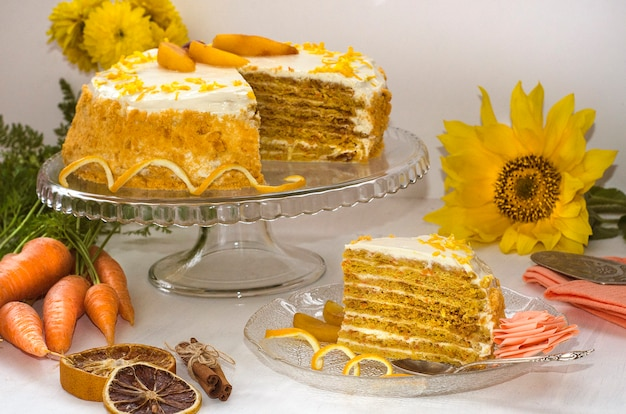 Carrot cake day. multilayer carrot cake on a white surface decorated with orange zest with yellow flowers and carrots. side view. homemade cakes