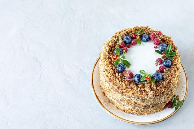 Морковный торт, украшенный ягодами и инжиром на белой тарелке. традиционная выпечка из ослицы.