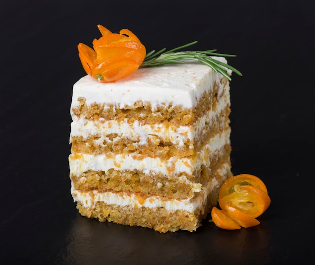 Carrot cake decorated with a branch of rosemary and kumquat