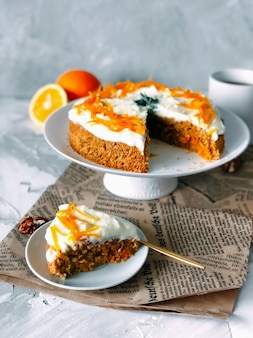 Carrot cake on a high white plate and a piece of cake on another plate on light marble background