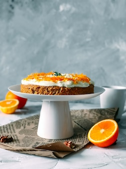 Carrot cake on a high white plate with half oranges around on grey wall background