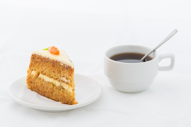 Carrot cake on white dish with hot drink