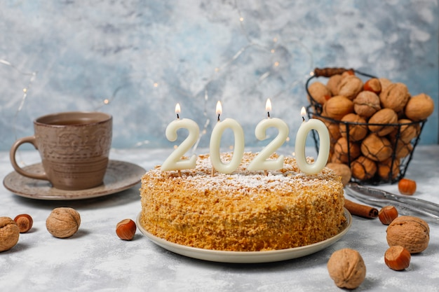 Carrot cake with 2020 candles and a cup of tea on grey concrete