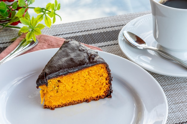 チョコレートのアイシングとコーヒーのカップを伴うキャロットケーキ。