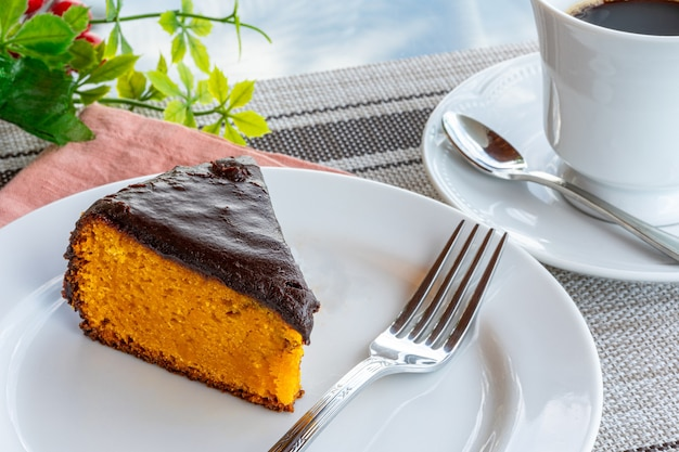 Carrot cake with chocolate icing, accompanied by a cup of coffee.