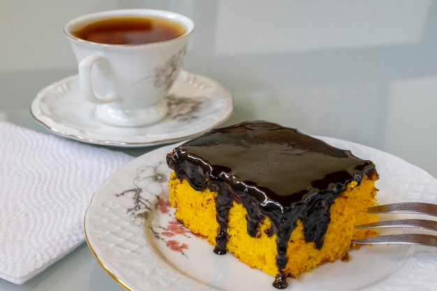 Carrot cake with chocolate icing and cup of tea