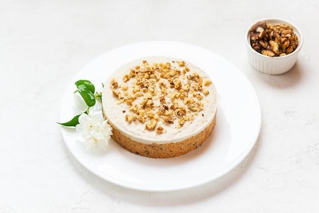 白いプレートにココナッツクリームとクルミを添えたキャロットケーキ生デザートベーキングなし