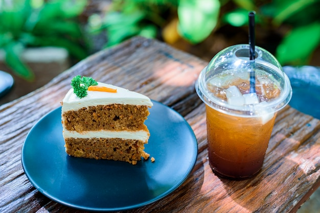 Carrot cake with coffee on a wooden table in the garden