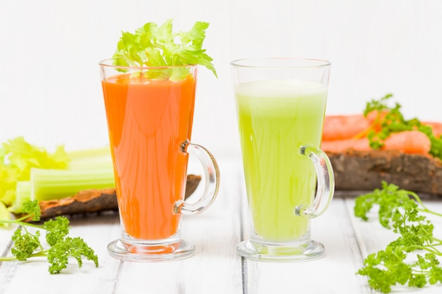 Carrot and celery juice with fresh vegetables on bark plates on wooden background