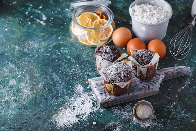 Carrot-chocolate muffin dusted with icing sugar, a cup of tea, baking ingredients. flour, eggs, lemon citrus on a dark table