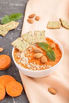 Carrot cream soup with sesame seeds and snacks in white bowl on a black concrete background. side view, close up.