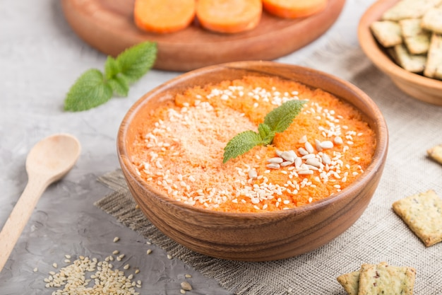 Carrot cream soup with sesame seeds and snacks in wooden bowl on a gray concrete background. side view, selective focus.