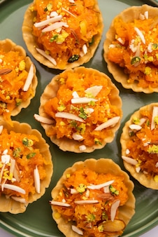 Carrot or gajar halwa canape or canapãƒâ© or fusion tart, garnished with dry fruits. indian dessert