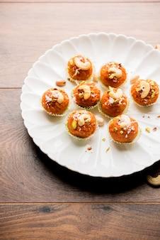 Морковная халва ладду или сладкие шарики, подается в тарелке с начинкой из сухофруктов. выборочный фокус