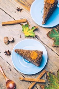 シナモンと木製の背景にスパイスで飾られたニンジン自家製ケーキ
