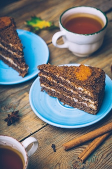 Carrot homemade cake with cinnamon and decorated with spices on wooden background.