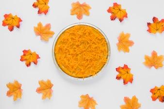 Carrot in plate between dry leaves