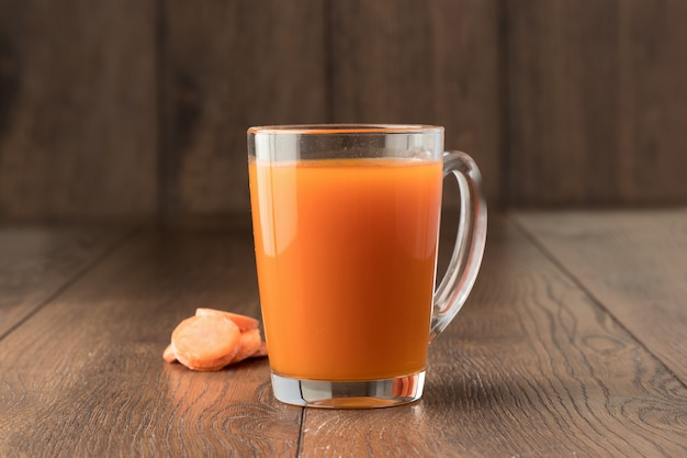 Carrot juice in a glass on wood