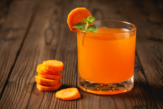 Carrot juice in glass on wooden table.