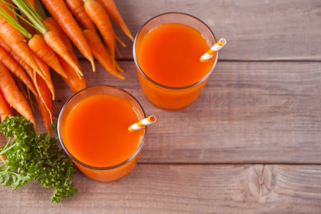 Carrot juice in glasses on wooden background