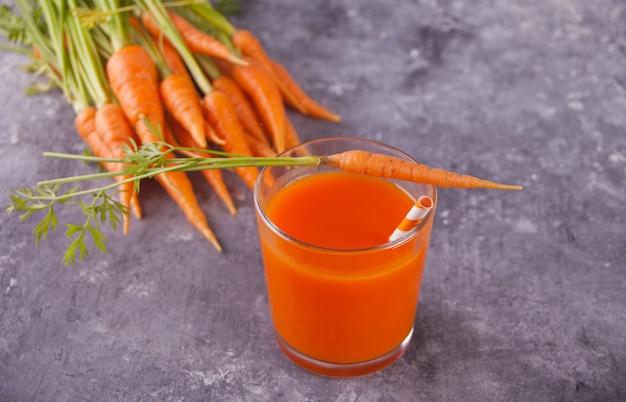 Морковный сок в стакане на бетонном фоне