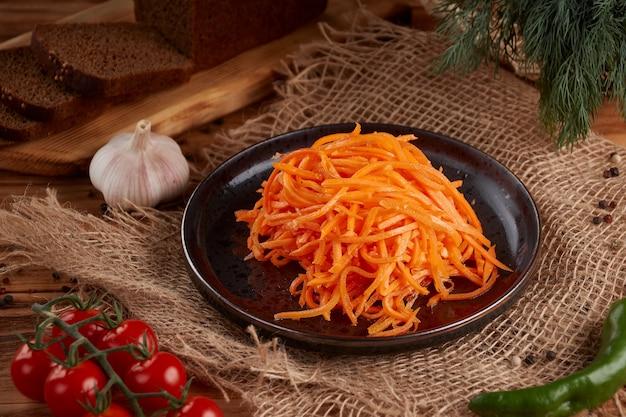 Морковный корейский салат в тарелке на деревянном
