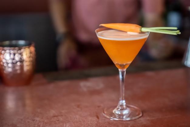 Морковный безалкогольный коктейль смешан и готов к подаче на красном батончике.