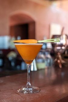 Carrot mocktail are mixed and ready to serve on red bar.