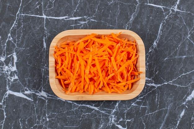나무 그릇에 샐러드 준비를위한 작은 강판에 당근.