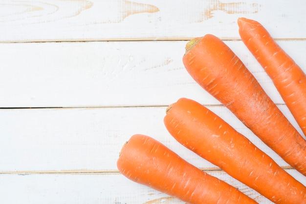 Морковь на белом деревянном столе.