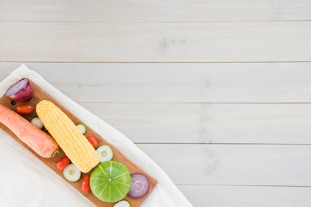 Carrot; onion; cherry tomatoes; cucumber; corn and gourd on chopping board over the napkin against wooden backdrop