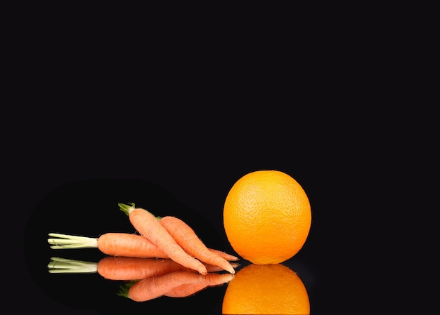 Carrot and orange on a black background