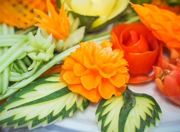 Carrot and other vegetable carved in flower shape on white plate.