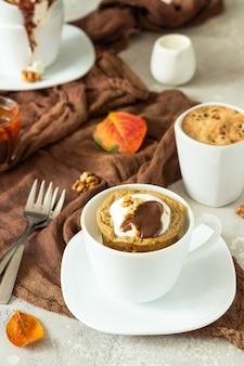 Carrot or pumpkin mug cupcake with whipped cream, caramel sauce and walnuts in a white ceramic mug.