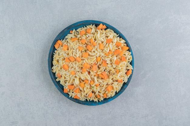 Рис с морковью в деревянной тарелке, на мраморе.
