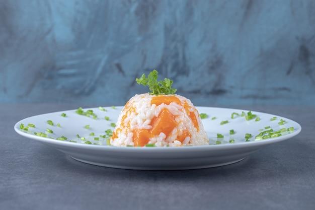 Рис с морковью на тарелке, на мраморной поверхности.