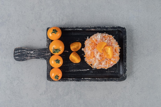 Carrot salad with yellow cherry tomatoes on a wooden board.