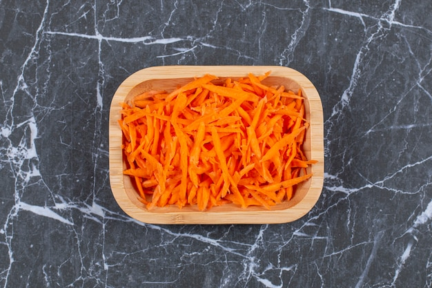 Carrot on a small grater for salad preparation in wooden bowl.