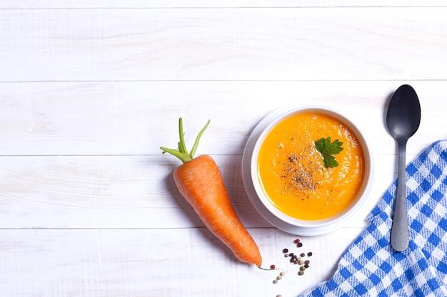 Чаша морковного супа с морковью на белом деревянном столе