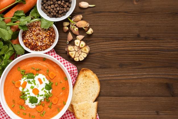 Морковный суп из свежемолотой моркови с зеленью и сметаной на деревянном пространстве.