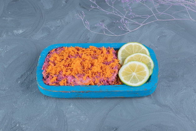 Carrot-topped walnut and beet salad with lemon slices on marble table.