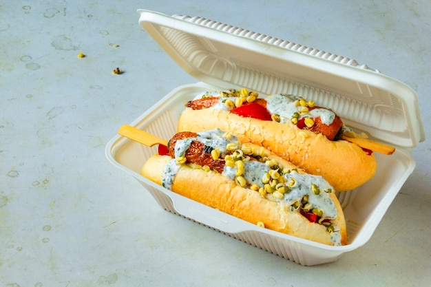 Carrot vegan hot dog. disposable tableware with vegetarian street food. healthy plant based meatless meal concept.