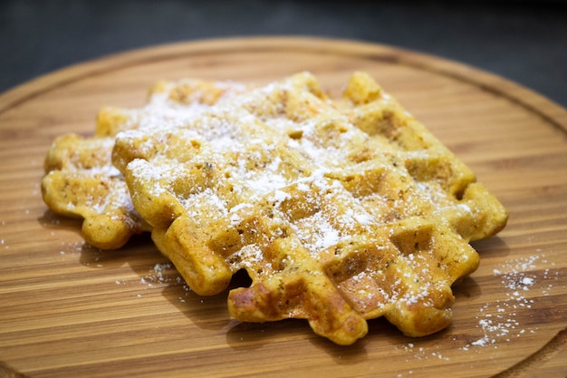 Carrot waffles with powdered sugar on a wooden board. perfect healthy breakfast.