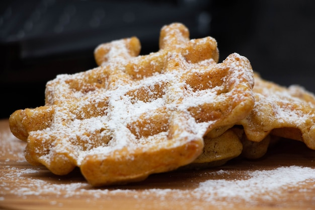 Carrot waffles with powdered sugar on a wooden board .
