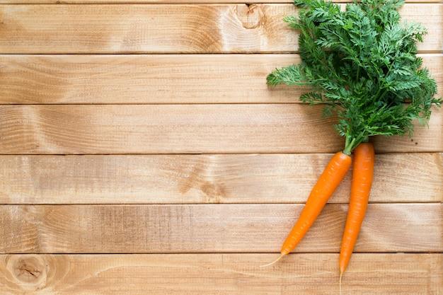 Морковь с зелеными листьями на деревянных фоне