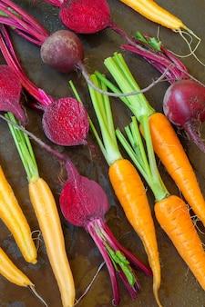 Выкладываем в ряд морковь и свеклу. металлический стол с ржавчиной и каплями воды